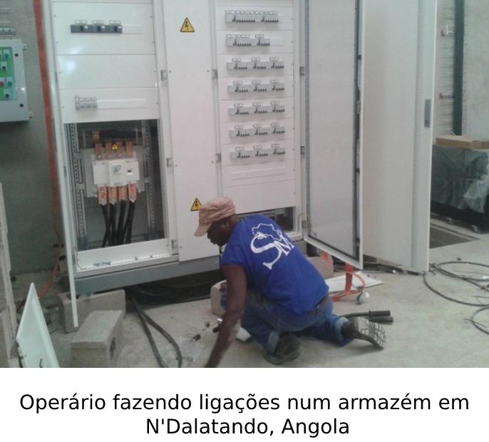 Operário fazendo ligações num armazém em N'Dalatando, Angola